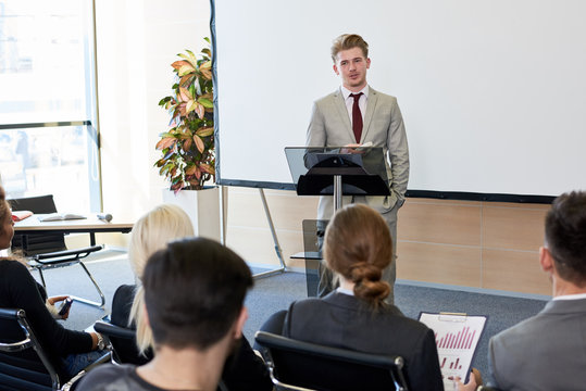 Portrait of young businessman standing by podium while giving speech at conference, copy space