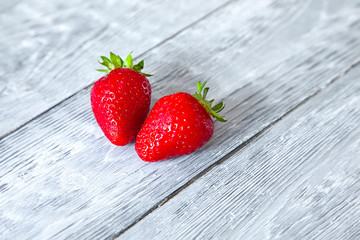 two fresh strawberries on a grey wooden table