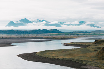 beautiful landscape with wide river and mountain peaks in clouds, iceland
