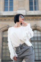 Woman in sunglasses pose in paris, france, fashion. Woman with brunette hair, red lips, makeup, beauty