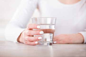 Female hand holding glass of water