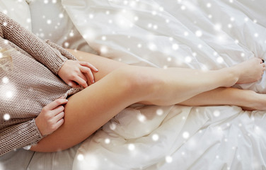 Fototapete - rest, sleeping, comfort and people concept - close up of young woman legs in bed over snow