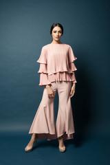 Attractive caucasian female model wearing elegant dress for work or dinner with blue background.Studio shot.