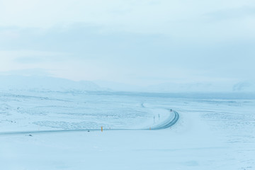 beautiful snow-covered landscape and road in thingvellir national park, iceland