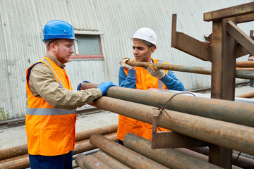 Portrait of two workers stacking metal pipes in warehouse of modern factory