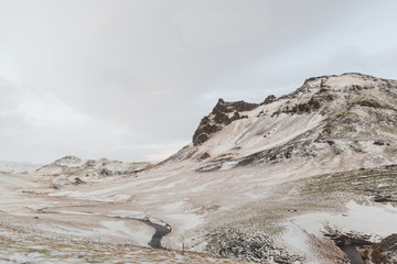 majestic icelandic view with snow-covered mountains and small river