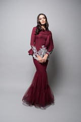 Attractive middle east female model wearing traditional dress.Dinner and eid mubarak fashion for Muslim Girl with grey background.