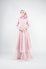 Attractive young Muslim girl wearing pink dress and hijab with grey background.Hijab Fashion Portraiture.