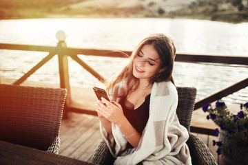 Cheerful relaxed woman uses smart phone for chat with friends, sits in modern coffee shop or terrace cafe. Pretty female reads good news on internet website, enjoys summer rest.