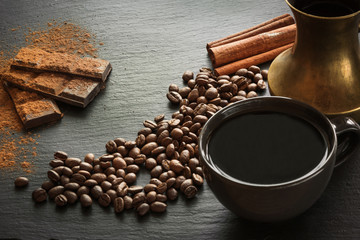 Cup of black coffee, coffee beans, chocolate bar, cinnamon and old copper cezve on black slate as...