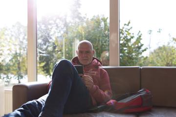 Older man in sofa using mobile phone