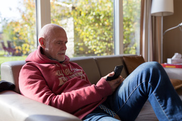 Senior man in living room couch with mobile phone