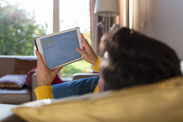 Man lying on sofa using digital tablet in living room at home