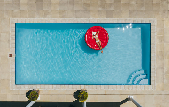 Woman sunbathing on inflatable mattress in pool.