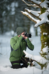 adventure photographer in a snowy forest