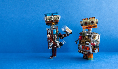 Robots communication, artificial intelligence concept. Two robotic characters, light bulb. Creative design toys on blue background. copy space
