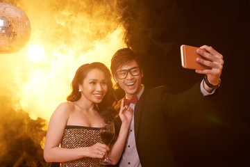 Cheerful Asian couple taking selfie on smartphone while enjoying party at night club, pretty woman holding glass of red wine in hand