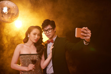 Group portrait of attractive young woman and her handsome boyfriend looking at camera while distracted from taking selfie on smartphone, interior of smoky nightclub on background