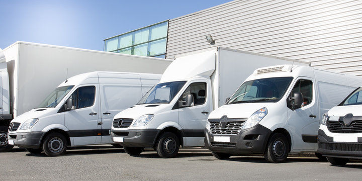 delivery white vans in service van trucks and cars in front of the entrance of a warehouse distribution logistic society