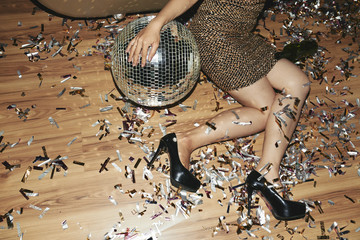 Unrecognizable young woman wearing lurex dress and high heels sitting on floor of modern nightclub and slightly embracing disco ball, colorful confetti scattered on floor