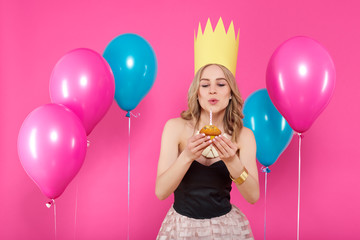 Gorgeous trendy young woman in party outfit and birthday crown blowing out candle on her birthday cupcake. Party, balloons and making a wish concept on pastel pink background.