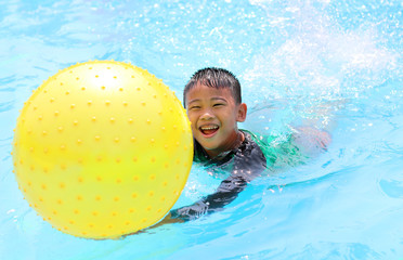 happy asian boy in green and black shirt swiming in clear blue water pool with yellow balloon ball