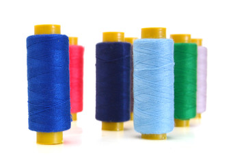 Spool of coloured thread isolated on white background.