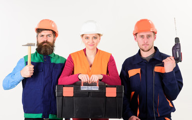 Portrait of confident carpenters carrying toolbox and tools