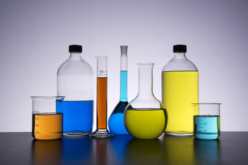 chemical bottles and graduated tube filled with colored liquids