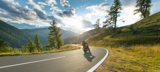 Motorcycle driver riding in Alpine highway, Nockalmstrasse, Austria, Europe. Wall mural