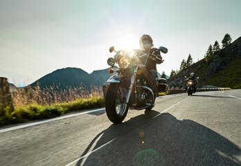 Motorcycle driver riding japanese high power cruiser in Alpine highway on famous Hochalpenstrasse, Austria.