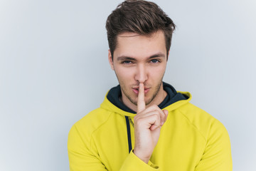 Serious sporty male dressed trendy in yellow hoodie, keeps finger on lips, making shh gesture for secret or be quiet. Isolated portrait of stylish man shows silence sign. People, emotion concept