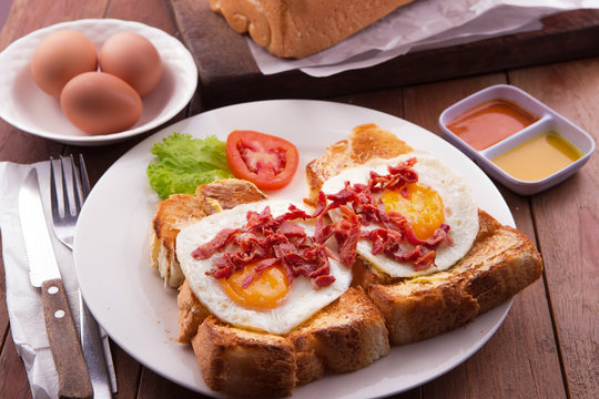 English Breakfast: toast, sunny side up eggs, bacon, ham and salad