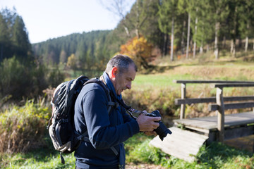 Mature man with backpack looking at pictures on camera in forest