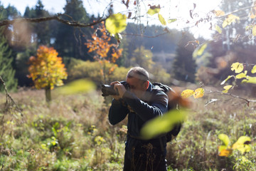 Senior man photographing autumn forest