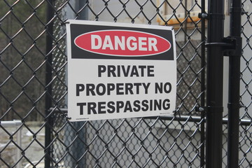 Danger private property sign on black fence at water dam