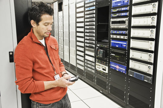 Caucasian male technician on a cell phone in a large computer server room.