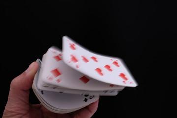 Hand lässt einen Stapel Karten springen