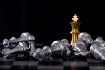 Business and leader concept, gold king chess with enemy losed and destroyed on board background.