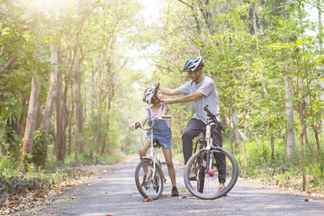 Happy father and daughter cycling in the park wears a bicycle helmet to his daughter, togetherness relaxation concept