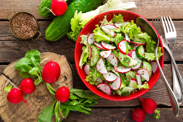 Fototapeta Vegetarian vegetable salad of radish, cucumbers, lettuce salad and flax seeds. Healthy  vegan food. Top view obraz