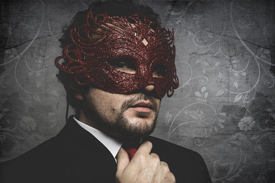 elegant and sexy man in suit and tie wearing a mysterious red and shiny mask, seduction concept