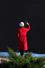 Woman in red coat making selfie on a sunny day. Back view