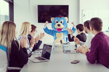 boss dresed as bear having fun with business people in trendy office