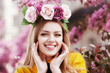 Outdoor close up portrait of young beautiful happy smiling girl posing in spring street with blooming pink trees. Model wearing circlet of roses, yellow blouse.