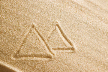 Egyptian pyramids are painted in the sand. Beach background. Top view. The concept of summer, summer kanikkuly, vacation, holydays.