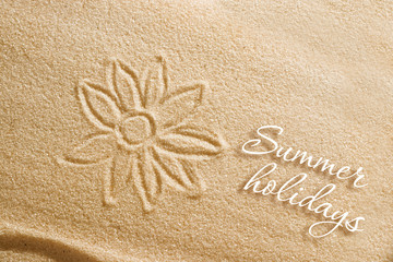 The flower is painted on the sand and the inscription is summer holidays. Beach background. View from above. The concept of summer, summer kanikkuly, vacation, holydays.