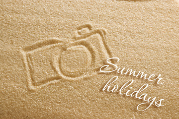 the camera is painted on the sand and the inscription is summer holidays. Beach background. View from above. The concept of summer, summer kanikkuly, vacation, holydays.