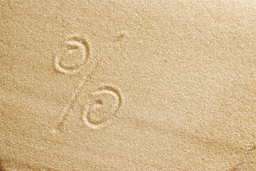 The percent sign is drawn in the sand. Beach background. Top view. The concept of summer, summer kanikkuly, vacation, holydays.