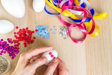 Hand holding easter polystyrene egg decorating pink sequins